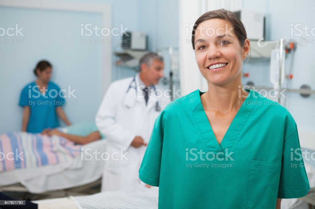 Nurse standing hospital room and smiling stock photo