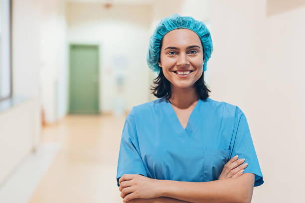 nurse standing in a medical clinic corridor - midwife stock pictures, royalty-free photos & images