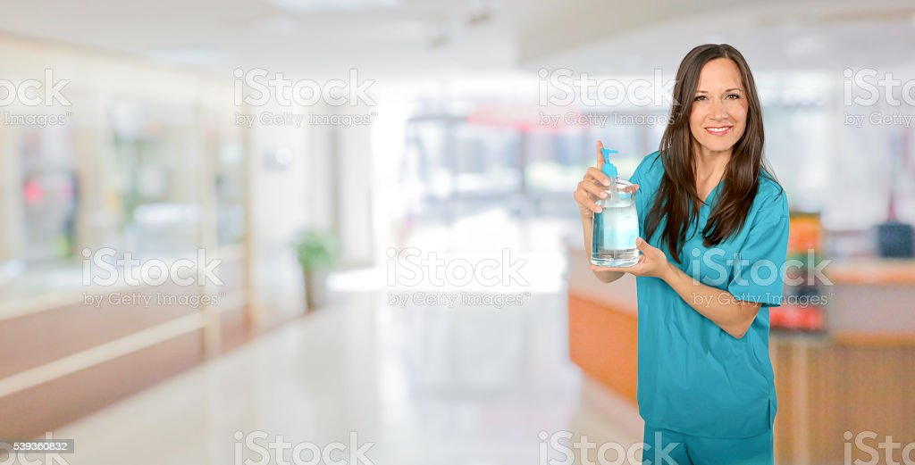 Nurse standing with hand sanitizer stock photo