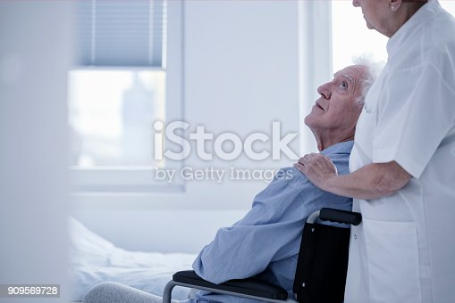 istock Nurse supporting disabled elderly man 909569728