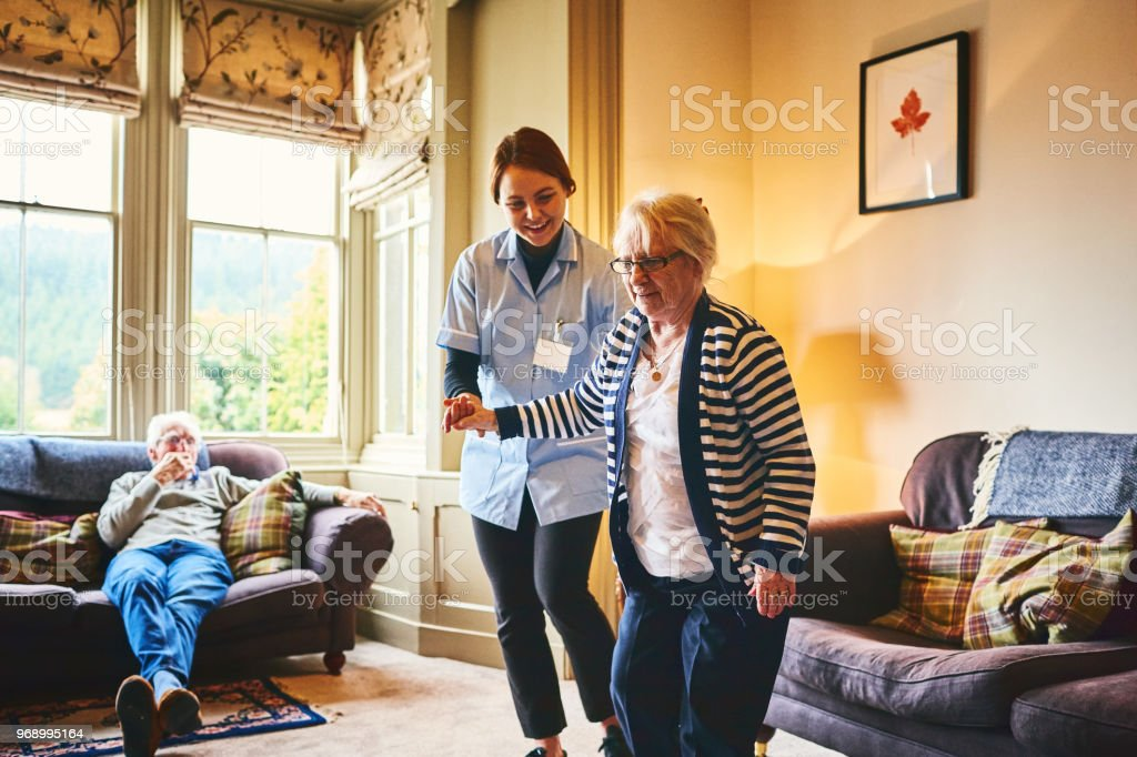 Krankenschwester tragende alte Frau drinnen gehen – Foto