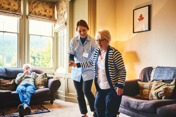 Nurse supporting old woman to walk indoors stock photo
