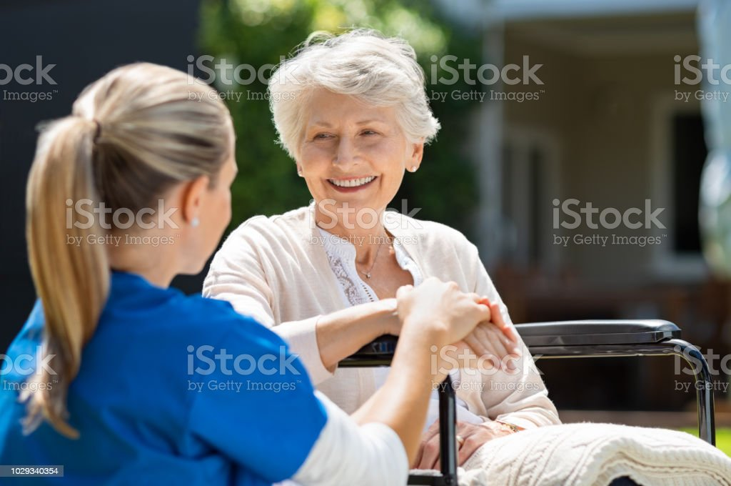 Nurse takes care of old patient stock photo