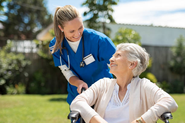 nurse takes care of old patient - female nurse stock photos and pictures