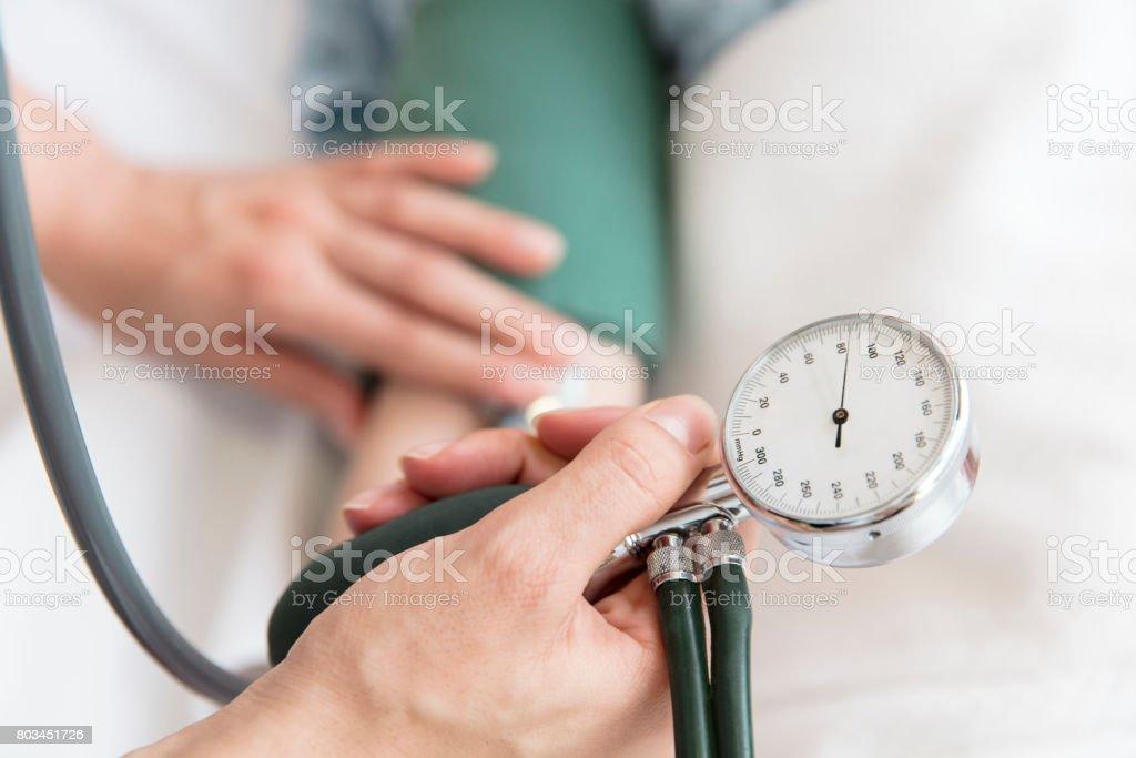 Enfermera toma la presión arterial del paciente - foto de stock