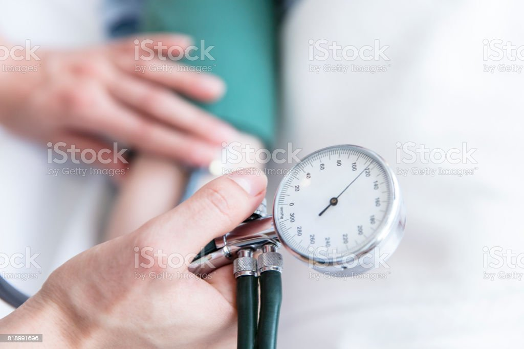 Nurse taking blood pressure of patient stock photo