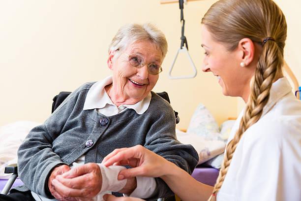 Nurse taking care of senior woman in retirement home stock photo