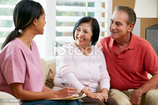 istock Nurse taking notes during a home wispy with senior couple 177780353