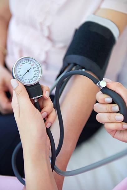 Krankenschwester, die alte mans Blutdruck – Foto