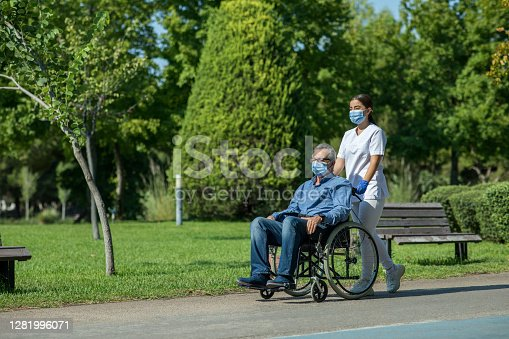 Nurse taking patient for a stroll in garden