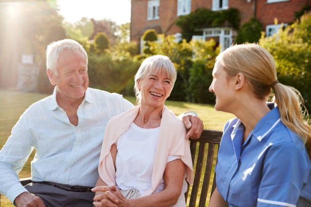 Nurse Talking To Senior Couple In Residential Care Home Nurse Talking To Senior Couple In Residential Care Home retirement community stock pictures, royalty-free photos & images