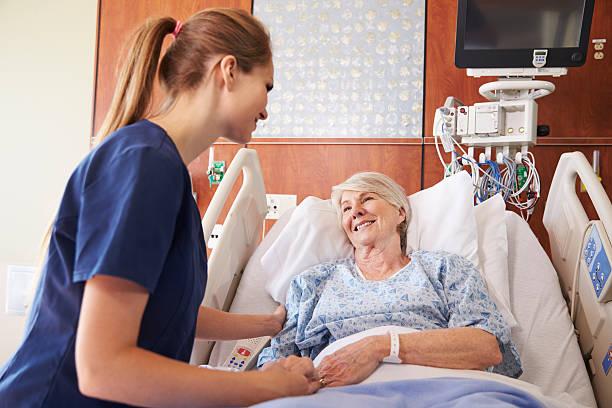 Enfermera hablando con un paciente Senior mujer en la cama de Hospital - foto de stock