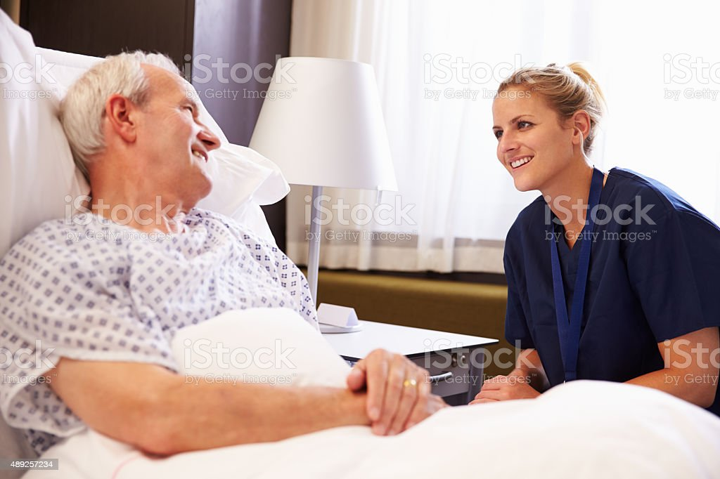 Nurse Talking To Senior Male Patient In Hospital Bed stock photo
