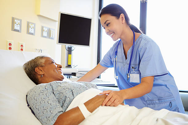 Nurse Talking To Senior Woman In Hospital Room Happy Smiling Nurse Talking To Senior Woman In Hospital Room bed furniture stock pictures, royalty-free photos & images