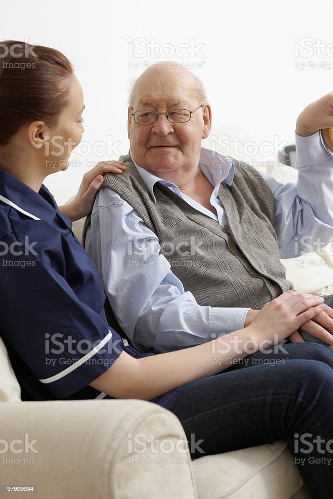 Nurse talking with aged man at home royalty-free stock photo