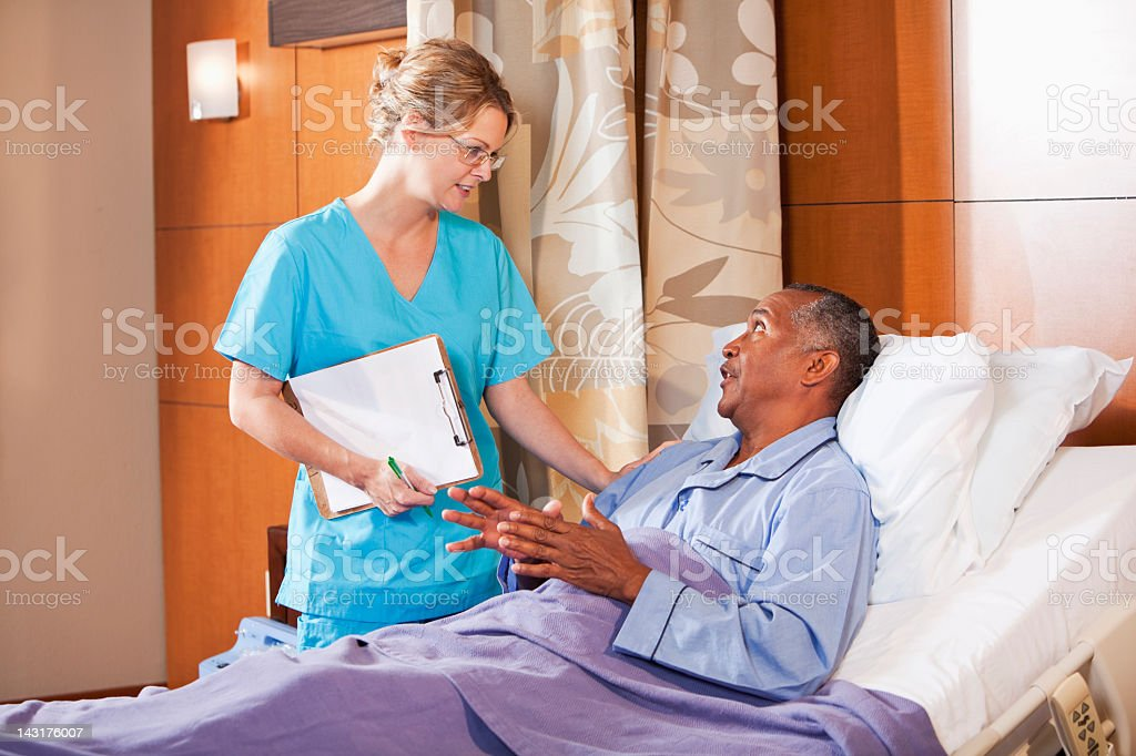 Nurse talking with patient in hospital bed royalty-free stock photo