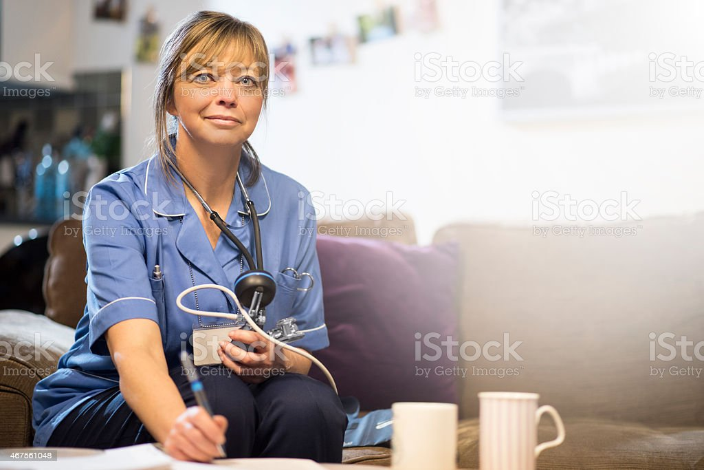 Nurse updates patient medical records on home visit stock photo