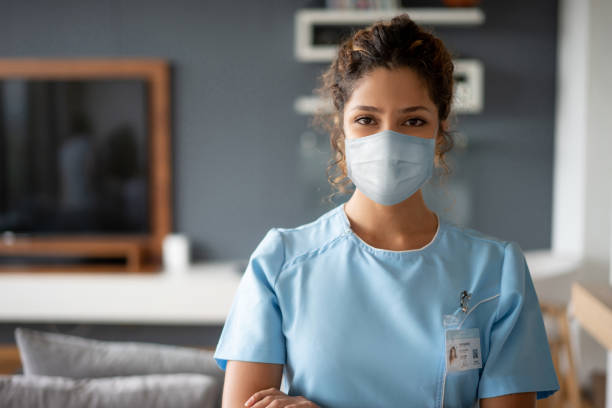Nurse using a facemask while making a house call during the COVID-19 pandemic stock photo
