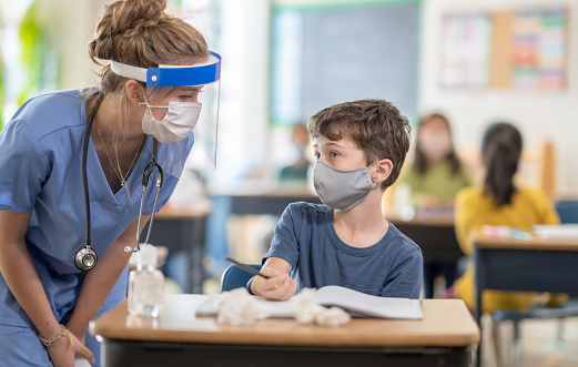 A female nurse is talking to an elementary school boy while he is sitting at his desk in a classroom.