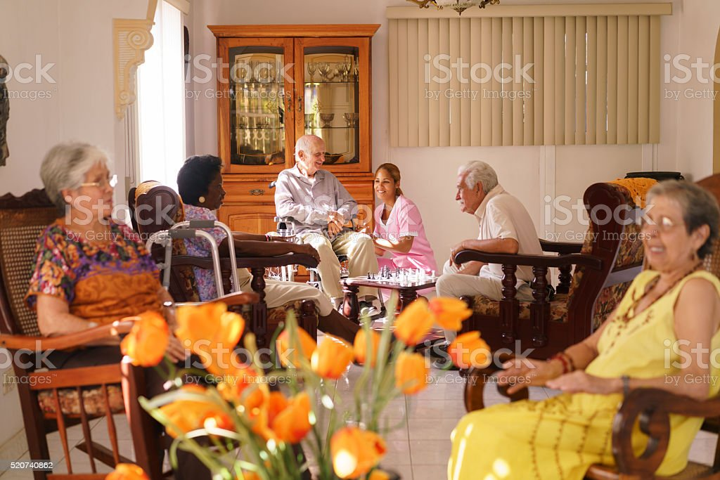 Nurse Visiting Old Man On Wheelchair In Hospice stock photo