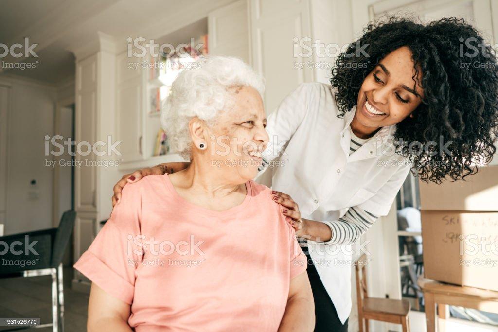 Nurse visiting senior lady at home stock photo