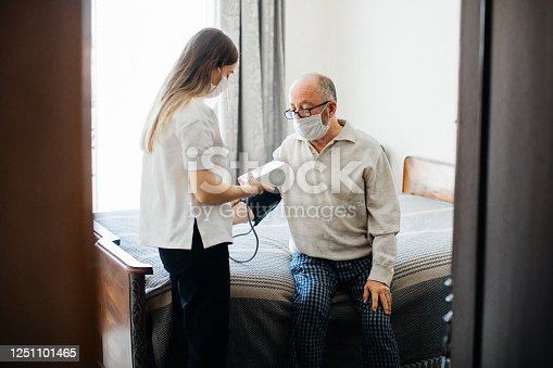 Young healthcare worker measuring blood pressure of a senior man at home