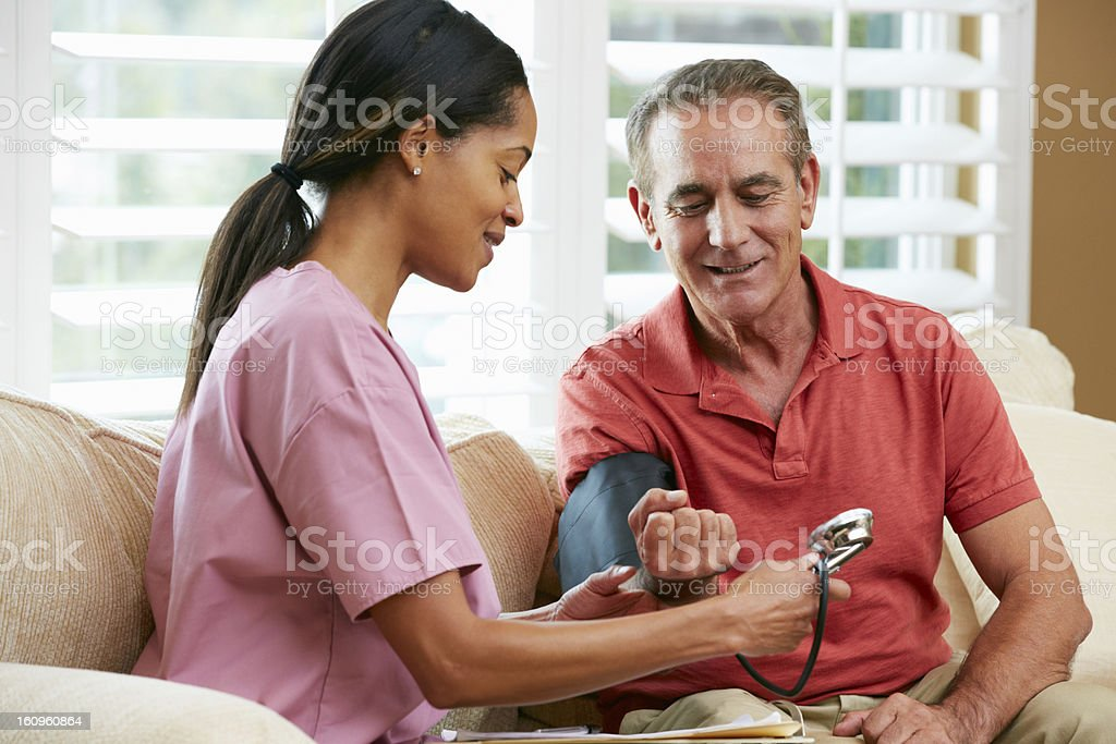 Nurse Visiting Senior Male Patient At Home royalty-free stock photo