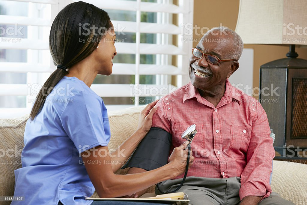 Nurse Visiting Senior Male Patient At Home Stock Photo -7129