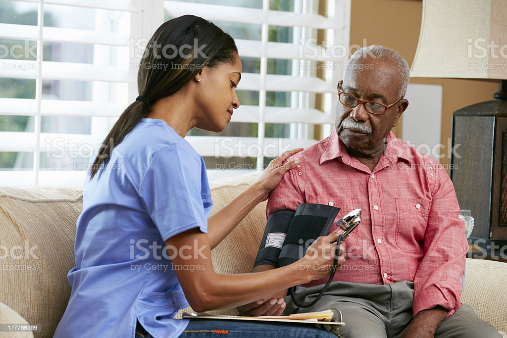 Nurse Visiting Senior Male Patient At Home stock photo