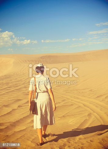 Young WWII Nurse Walking In The Desert With Her back To The Camera. She wears an authentic female medical dress uniform and carries a leather shoulder bag. There is lots of copy space in the sky