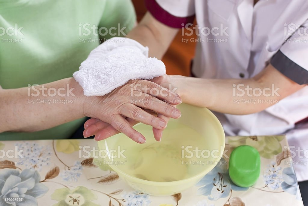 nurse washes old patients hands stock photo