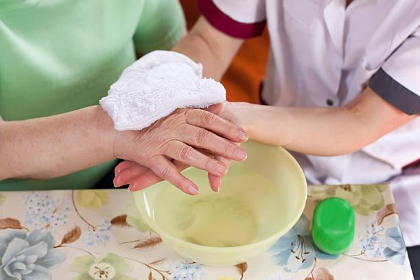 infermiere lavaggi vecchio pazienti le mani - prodotto per l'igiene personale foto e immagini stock