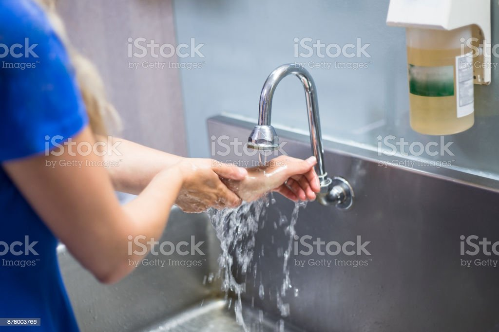 Nurse washing her hands in a hospital stock photo