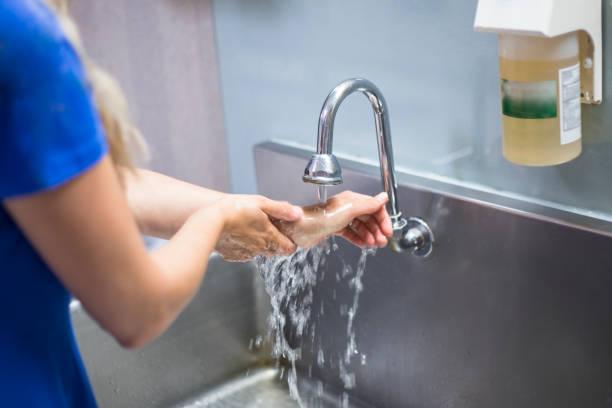 waschen sie ihre hände in einem krankenhaus krankenschwester - wasch oder spülbecken stock-fotos und bilder