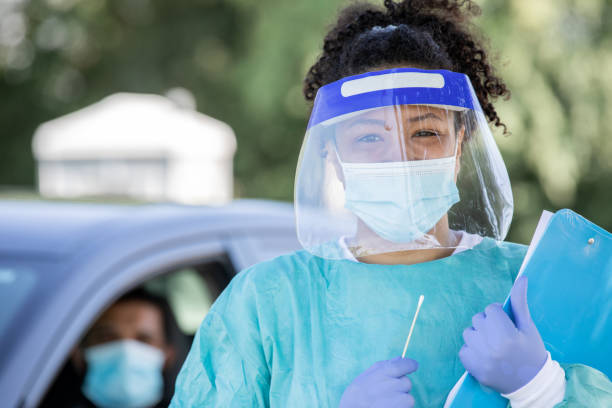 Nurse wearing PPE smiles at drive through testing site stock photo