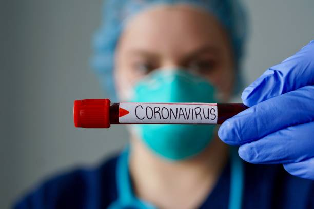 nurse wearing respirator mask holding a positive blood test result for the new rapidly spreading coronavirus, originating in wuhan, china - covid zdjęcia i obrazy z banku zdjęć