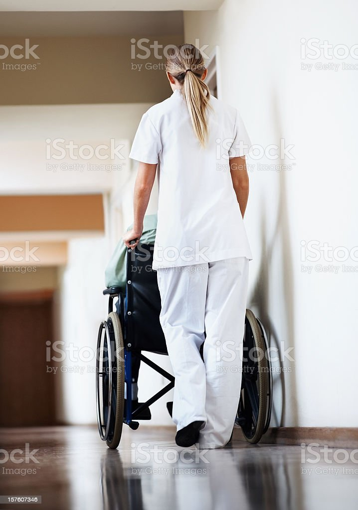 Nurse with a patient sitting in wheelchair at hospital corridor royalty-free stock photo