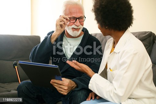 Senior man with a female doctor at his home. About 70 years old Caucasian male and a 35 years old African female.