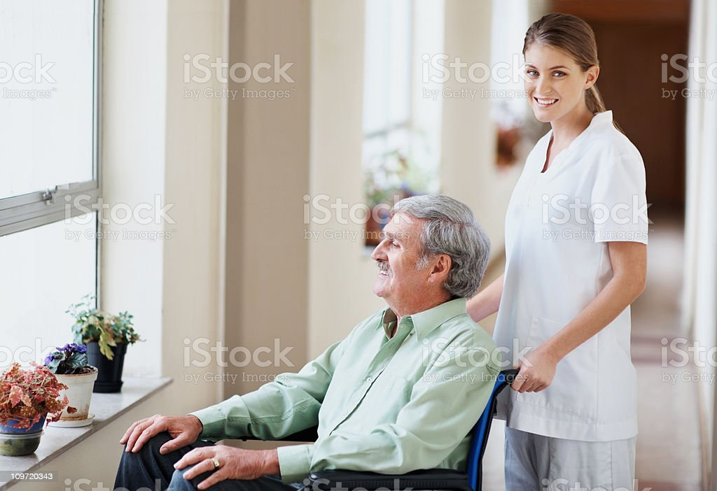 Nurse with an old man in wheelchair looking through window royalty-free stock photo