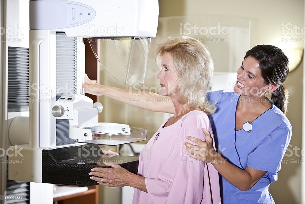 Nurse with patient getting mammogram stock photo