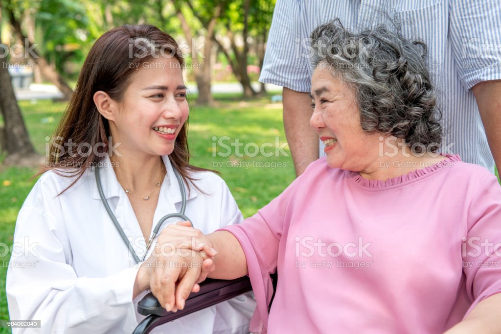 Nurse with senior patient in park. Senior disable woman in wheelchair relaxing and being comfort by a chinese female nurse. - Royalty-free Adult Stock Photo