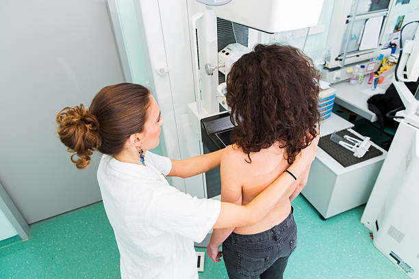 nurse with young women having a mammography - screening stock photos and pictures