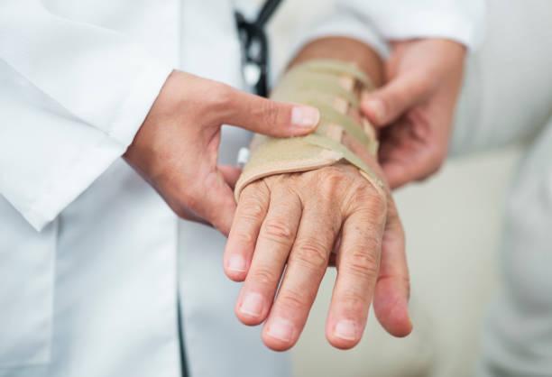 Krankenschwester Umhüllung verletzten Handgelenk Of Senior Woman – Foto