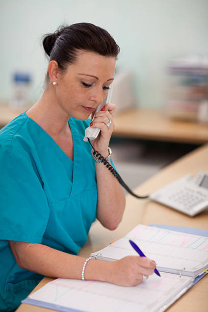 nurse writes an appointment in the calendar - nurse on phone stock photos and pictures