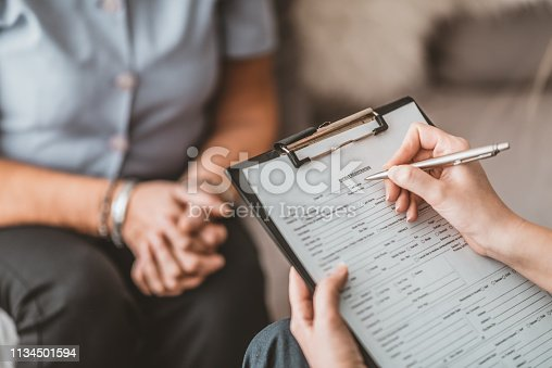 Medicine, age, health care and people concept - Photo of doctor or nurse with clipboard writing prescription for senior woman at hospital or home. Female Nurse writing on clipboard while interacting with a patient in hospital. Nurse Visiting Senior woman For Check Up. Young nurse and elderly woman at home. Doctor receiving patient registration form in hospital