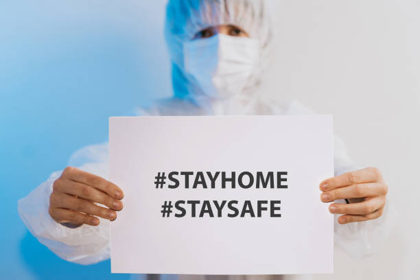 Nurse/Doctor holding a paper with a message for people to stay at home stock photo