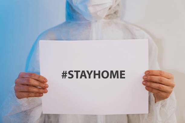 Nurse/Doctor holding a paper with a message for people to stay at home Nurse/Doctor holding a paper with a message for people to stay at home. Copy space for change the text on the paper. flatten the curve stock pictures, royalty-free photos & images