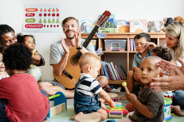Nursery children playing with musical instruments in the classroom Nursery children playing with musical instruments in the classroom preschool teacher stock pictures, royalty-free photos & images