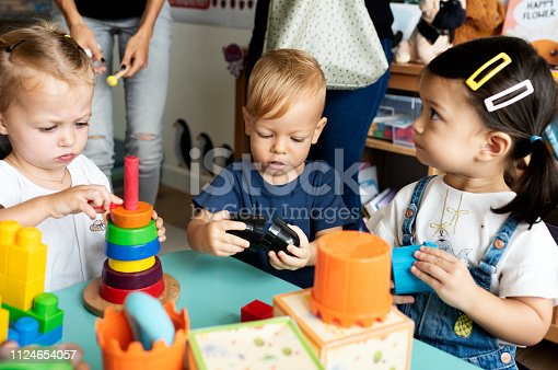 istock Nursery children playing with teacher in the classroom 1124654057