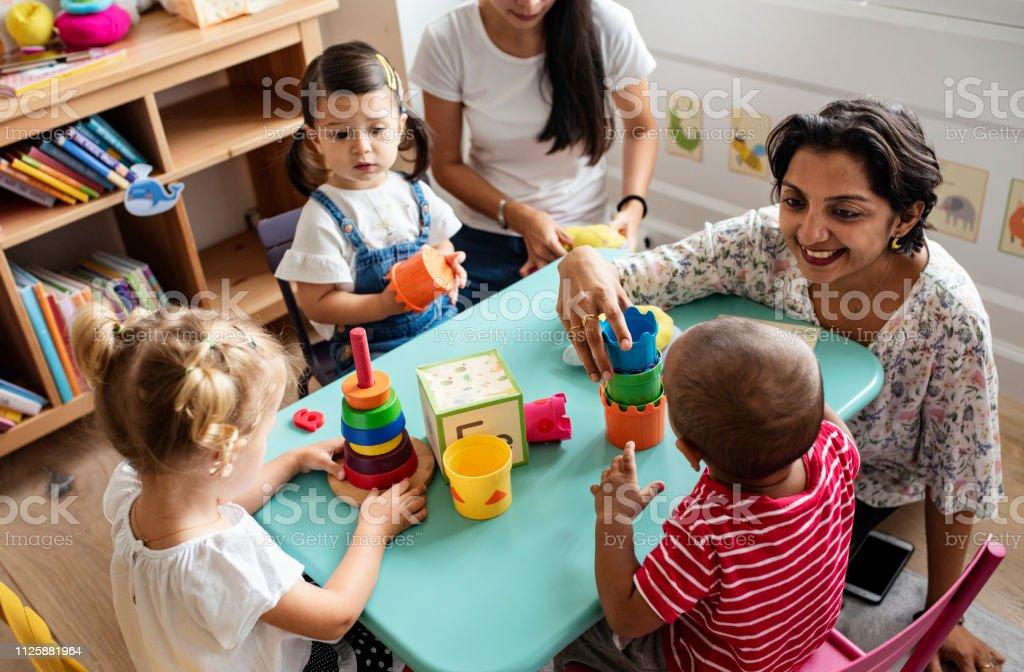Crianças de berçário brincando com professor em sala de aula - Foto de stock de Aluno de Jardim de Infância royalty-free